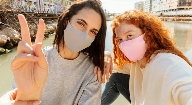 Dwie koleżanki z maskami na twarz na zewnątrz razem biorąc selfie