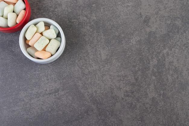 Dwie kolorowe miski gum do żucia na kamiennym stole.