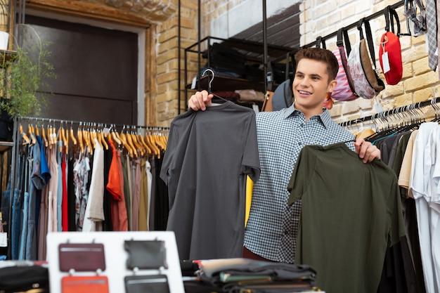 Dwie koszulki. pozytywny młody człowiek uśmiecha się i szuka zadowolony, trzymając dwie koszulki i robi zakupy