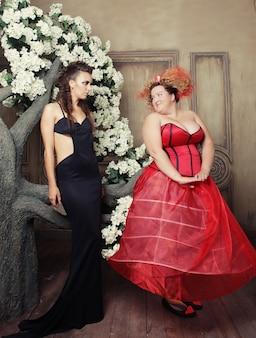 Dwie królowe w karnawałowych strojach. czarny i czerwony. zdjęcie z wakacji.