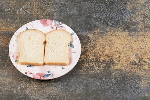Dwie kromki chleba na kolorowym talerzu.