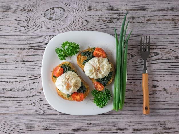 Dwie kromki chleba tostowego z jajkami w koszulce i ziołami na białym talerzu. wegetariańska przekąska z jajkiem w koszulce. widok z góry.