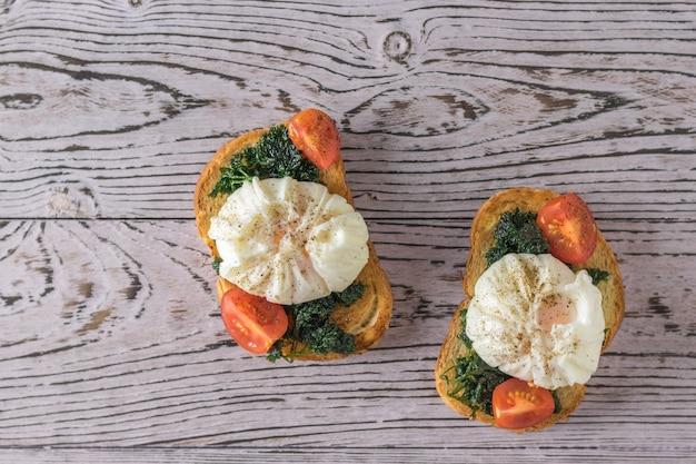 Dwie kromki chleba tostowego z jajkami w koszulce na drewnianym stole. wegetariańska przekąska z jajkiem w koszulce. widok z góry.