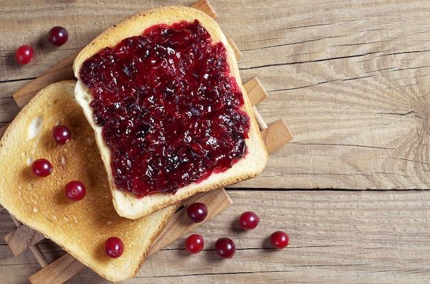 Dwie kromki chleba tostowego z konfiturą żurawinową i jagodami