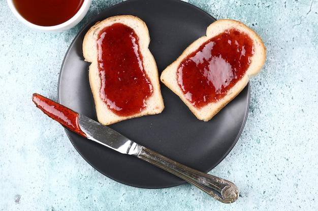 Dwie kromki chleba z dżemem truskawkowym w czarnej płycie.