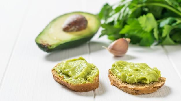Dwie kromki chleba z guacamole i awokado na białym stole. dieta wegetariańska meksykańskie jedzenie awokado. surowe jedzenie.