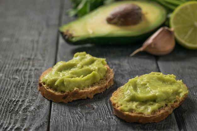 Dwie kromki chleba z guacamole z awokado i czosnkiem. dieta wegetariańska meksykańskie jedzenie awokado. surowe jedzenie.