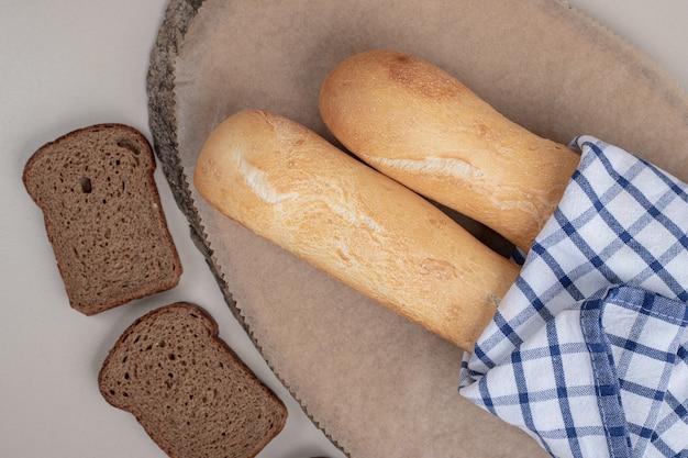 Dwie kromki ciemnego chleba z francuskimi bagietkami. wysokiej jakości zdjęcie