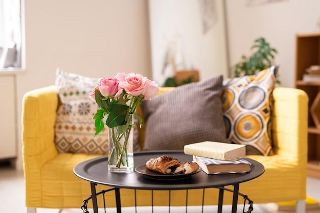 Dwie książki, świeży rogalik na talerzu i kilka różowych róż w szklance wody na małym stoliku z kanapą