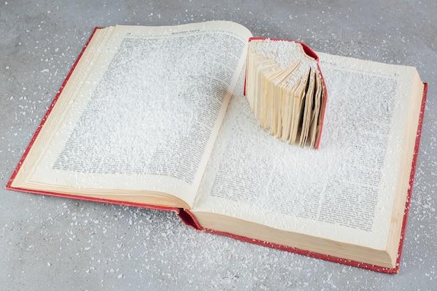 Dwie książki wystawione na marmurowej powierzchni pokrytej proszkiem kokosowym