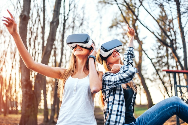 Dwie ładne dziewczyny cieszą się okularami rzeczywistości wirtualnej na zewnątrz