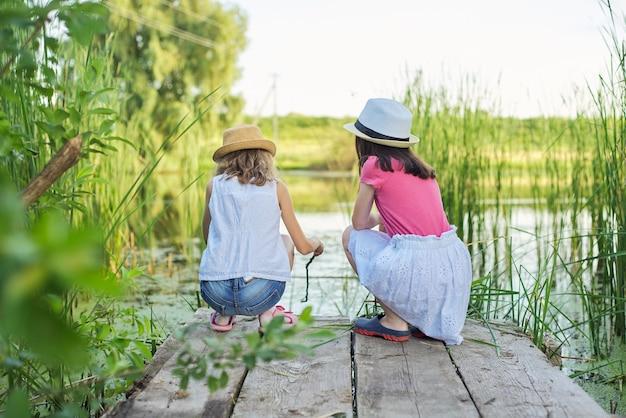 Dwie ładne dziewczyny dzieci siedząc na drewnianym molo nad jeziorem w trzcinach, bawiąc się wodą, rozmawiając, widok z tyłu. wakacje, przyroda, szczęśliwe dzieciństwo, przyjaźń, wiejski styl.