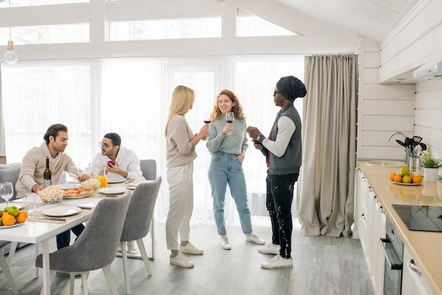 Dwie ładne dziewczyny i afrykanin z czerwonym winem stoją w kuchni i rozmawiają, podczas gdy ich przyjaciele siedzą przy stole