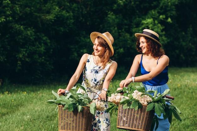 Dwie ładne dziewczyny idą z rowerami w parku wiosny o zachodzie słońca. dziewczyny bawią się, śmieją, uśmiechają i jeżdżą na rowerach. portret dwóch młodych kobiet w sukienki i kapelusze ze słomy. aktywne wakacje letnie