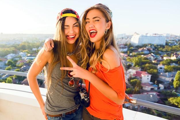 Dwie ładne dziewczyny mody wysyłają buziaki i bawią się, ubrane w jasne czapki i okulary przeciwsłoneczne