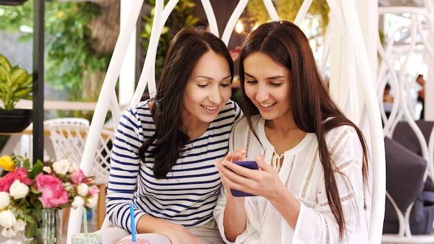 Dwie ładne dziewczyny śmieją się podczas przeglądania zdjęć na telefonie siedząc w kawiarni.