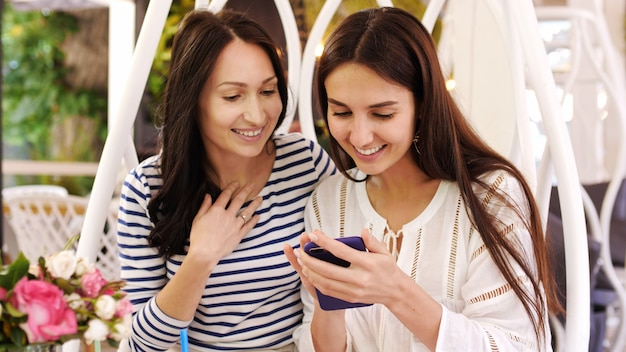 Dwie ładne dziewczyny śmieją się podczas przeglądania zdjęć na telefonie w kawiarni.