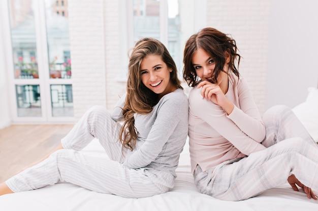 Dwie ładne dziewczyny w piżamie siedzące plecami do siebie na łóżku w jasnym pokoju. uśmiechają się.
