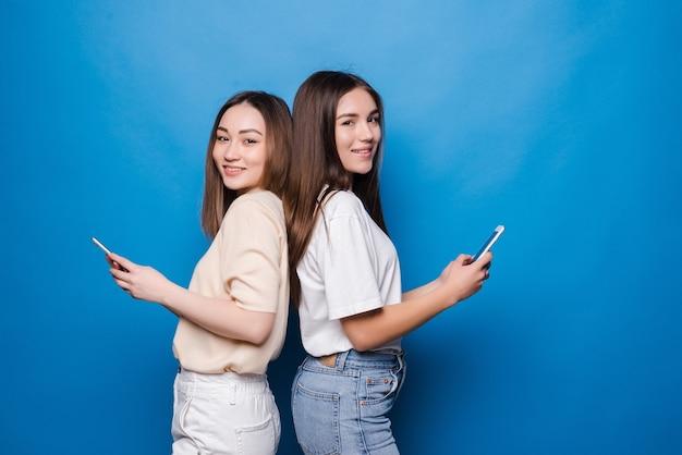 Dwie ładne kobiety korzystające z telefonów komórkowych na niebieskiej ścianie