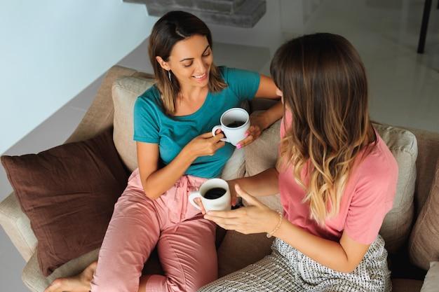Dwie ładne kobiety rozmawiają i piją herbatę, siedząc na kanapie w nowoczesnym domu