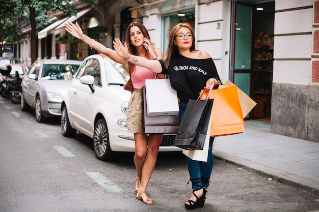 Dwie ładne kobiety wędrują taksówką