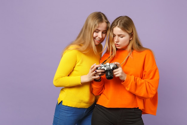 Dwie ładne młode dziewczyny siostry bliźniaczki blond w żywe kolorowe ubrania trzymając aparat retro vintage na białym tle na fioletowej ścianie niebieski. koncepcja życia rodzinnego osób.