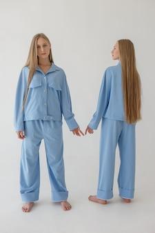 Dwie ładne młode siostry bliźniaczki ze stawianiem długich blond włosów
