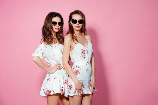 Dwie ładne przyjaciółki w letnich sukienkach