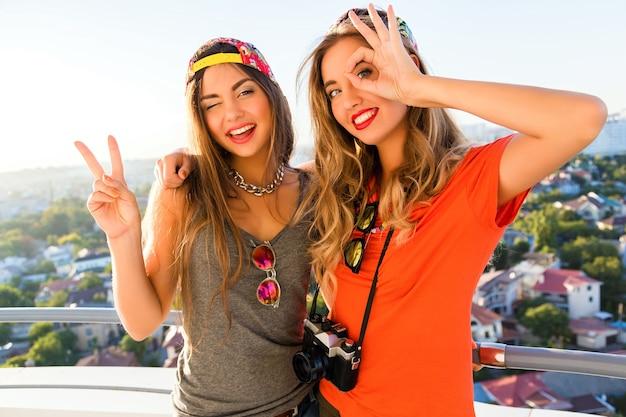 Dwie ładne przyjaciółki, wesołe dziewczyny, które bawią się i robią śmieszne, szalone miny na dachu