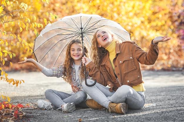 Dwie ładne siostry idące razem jesienią. wesoły dziewczyny koncepcja upadku.