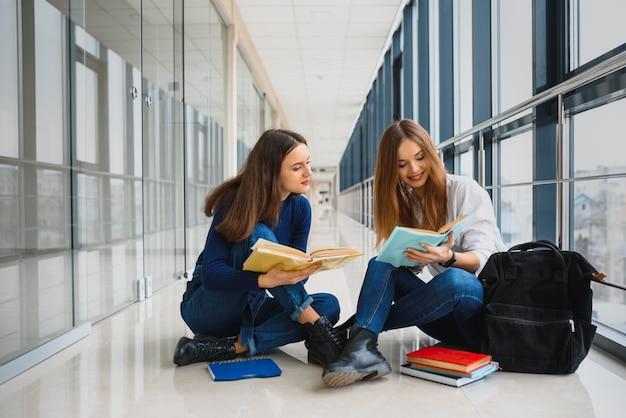 Dwie ładne studentki z książkami siedzą na podłodze w korytarzu uniwersytetu