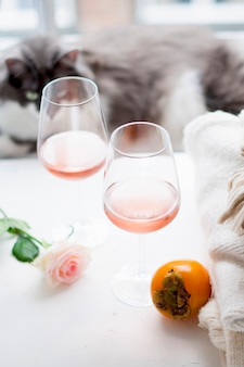 Dwie lampki wina i duży bukiet róż i kot domowy przy oknie. wolne miejsce na tekst.