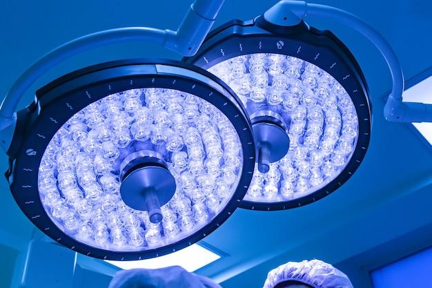 Dwie lampy chirurgiczne na sali operacyjnej mają niebieski filtr