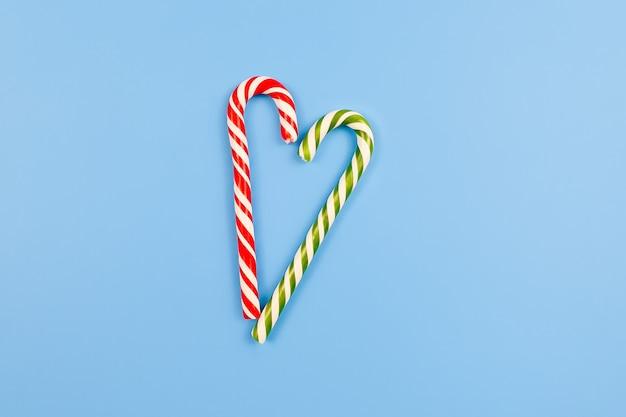 Dwie laski cukierków miętowych w paski w świątecznych kolorach na niebieskim stole. znak serca