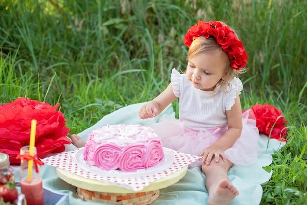 Dwie lata dziewczyna siedzi w pobliżu dekoracje uroczystości i jedzenie jej tort urodzinowy. ciasto smash.