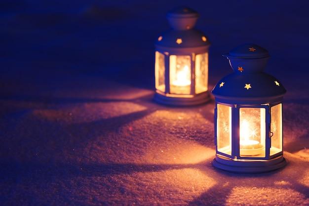 Dwie latarnie z płonącą świeczką na śniegu wieczorem. przyciemniane zdjęcie