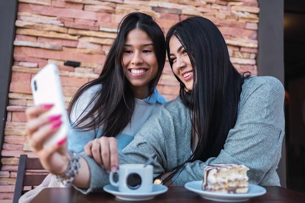Dwie latynoskie przyjaciółki robią sobie selfie w barze na świeżym powietrzu.