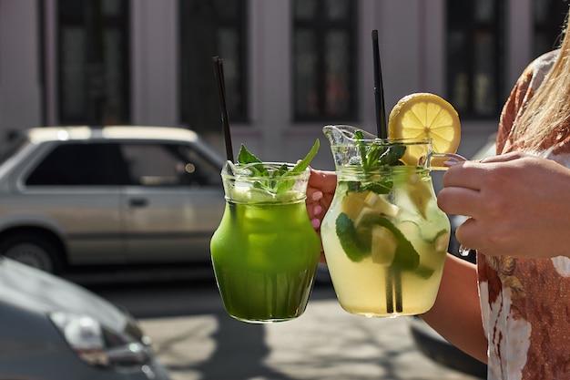 Dwie lemoniady w rękach dziewczynki. świeże napoje z ogórków i cytryny.