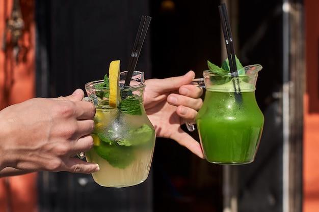 Dwie lemoniady w rękach mężczyzny. świeże napoje z ogórków i cytryny.