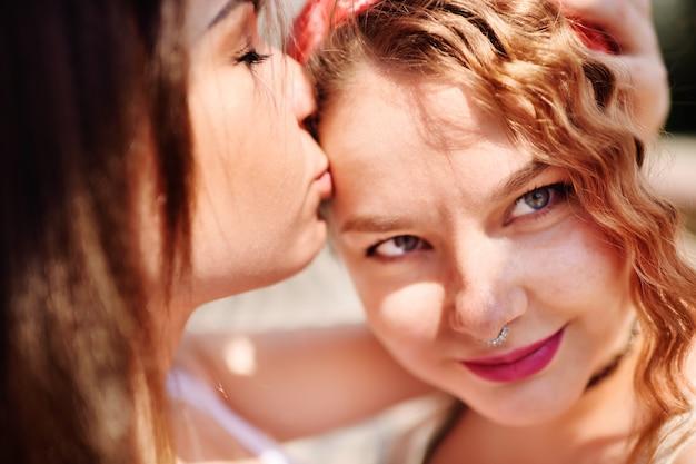 Dwie lesbijki delikatnie przytulają się i całują. koncepcja lgbt, seks mniejszości, miłość, równość