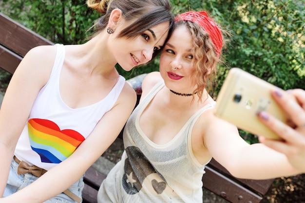 Dwie lesbijki dziewczyny rozładowują się na telefonach z aparatem fotograficznym lub robią sobie selfie i uśmiechają się.