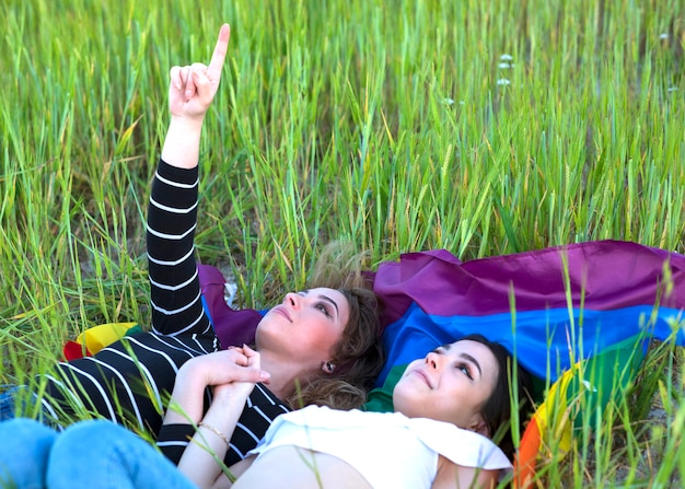 Dwie lesbijki leżące na trawie z flagą dumy gejowskiej