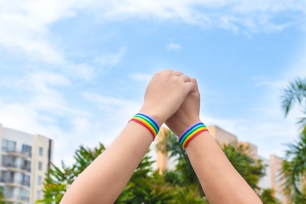 Dwie lesbijki trzymające się za ręce noszące flagę dumy