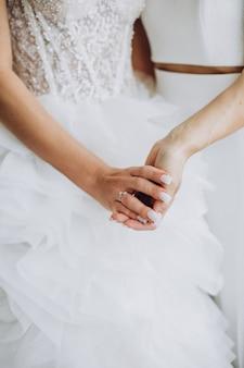 Dwie lesbijki trzymające się za ręce z bliska w dniu ślubu