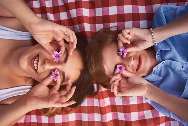 Dwie leżące kobiety zasłaniają oczy polnymi kwiatami