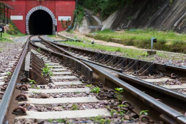 Dwie linie kolejowe zbiegają się w jedną stronę w kierunku czerwonego tunelu. stalowa kolej na pociągi
