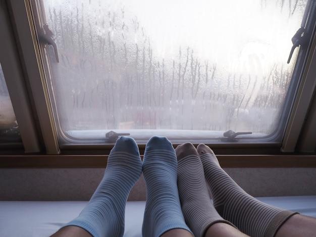 Dwie ludzkie stopy w skarpetkach z paskiem na łóżku obok okna