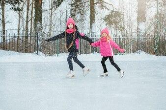 Dwie Małe uśmiechnięte dziewczyny jeżdżące na łyżwach na lodzie w kolorze różowym i ręcznie robione szaliki.