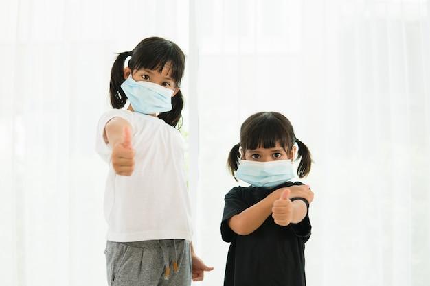 Dwie małe azjatki noszące maskę do ochrony pm2.5 i pokazujące gest kciuka w górę dla dobrego powietrza na zewnątrz