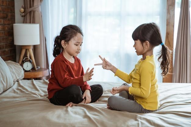 Dwie małe azjatyckie dziewczynki uśmiechały się radośnie, grając w papierowe nożyczki